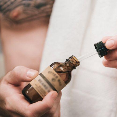 Флакон масла для бритья в руках
