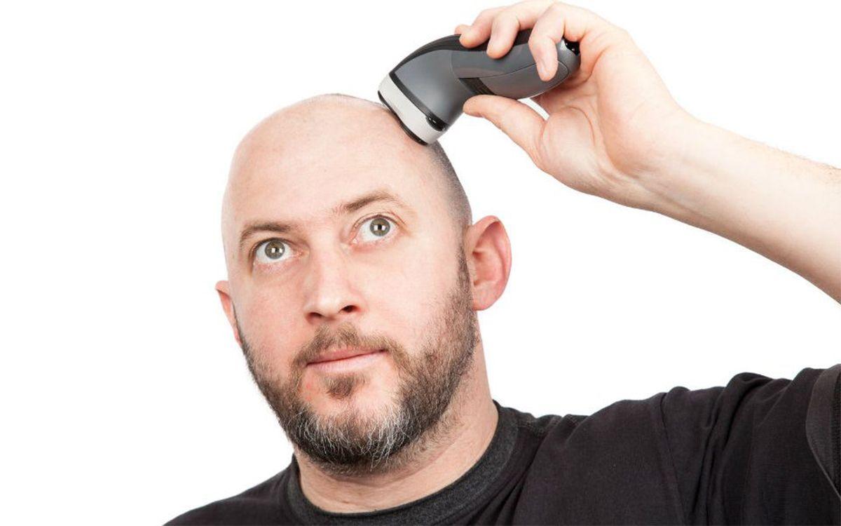 Мужчина бреет голову электробритвой