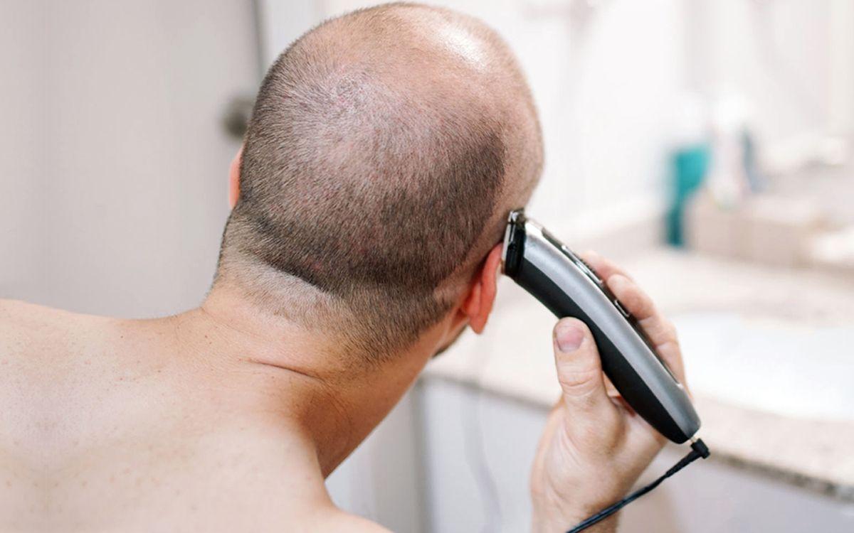 Мужчина бреет голову машинкой для стрижки волос