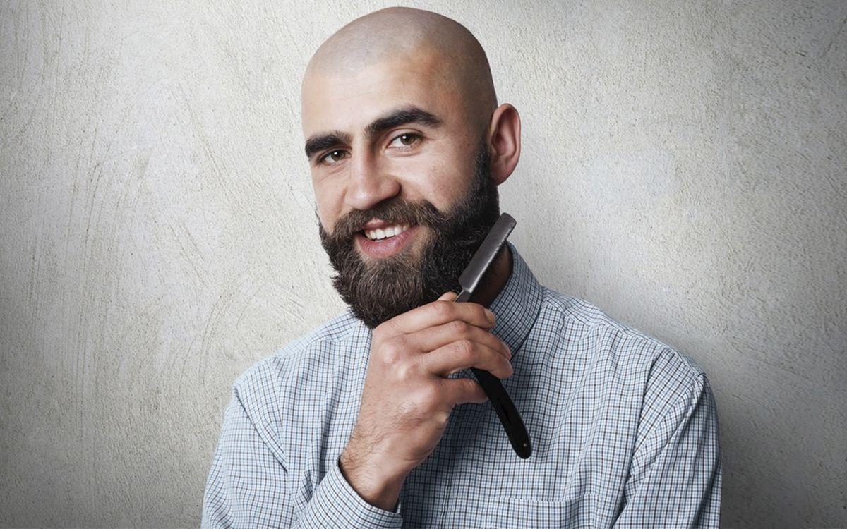 Лысый мужчина с бородой держит опасную бритву в руке