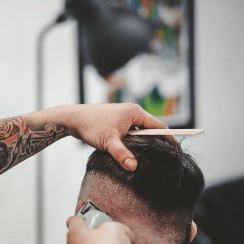 Мужчина сбривает волосы машинкой до щетины