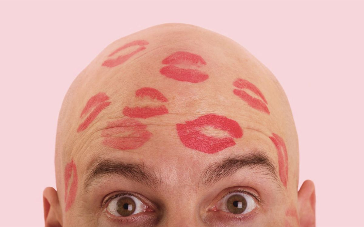 Поцелуи помады на лысой голове мужчины